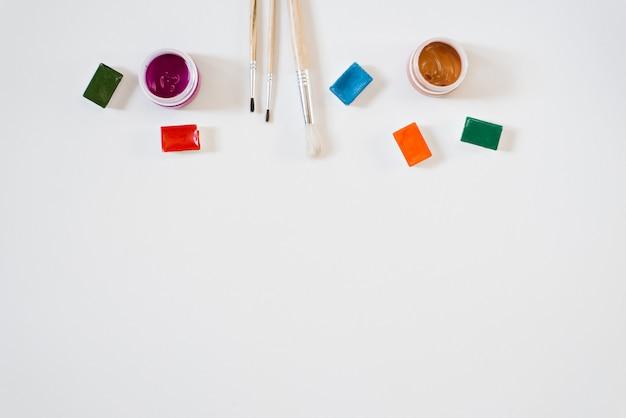 溝、ブラシ、白い背景にさまざまな色のガッシュと瓶の水彩絵の具の境界線。コピースペース。アートスクールまたはコース、ドローイングのマスタークラス