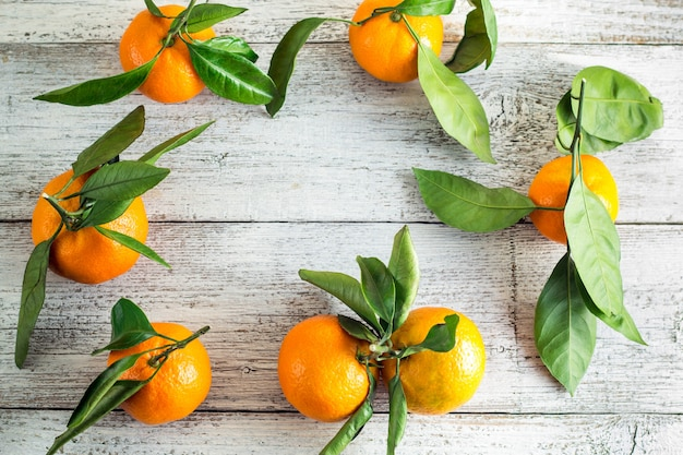 Border of orange tangerines with green leaves on white wooden surface. top view and copy space.