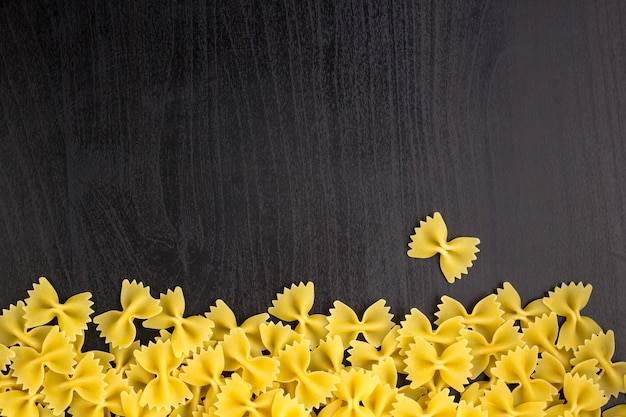 Border of a pile of farfalle pasta on black background with copyspace