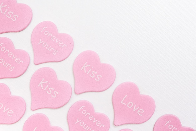 Border pink hearts with text love, kiss, forever yours on white background with copy space