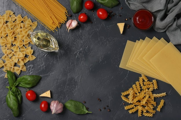 Border of raw pasta durum wheat, tomato sauce, cherry tomatoes, basil and spice on dark gray. view from above. flatlay style.
