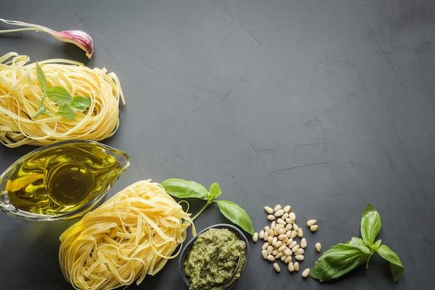 Border of raw pasta, pesto, basil, parmesan for cooking mediterranean dishes.