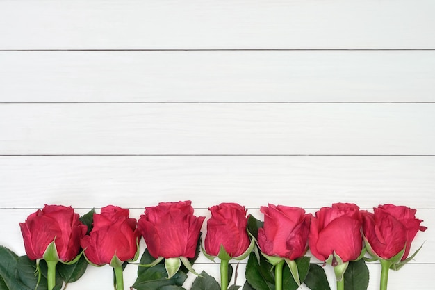 Border of red roses on white wooden background. top view, copyspace.