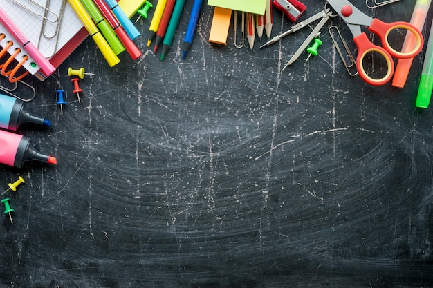 Border of school supplies on a chalkboard background. free space