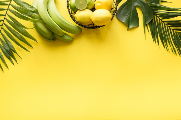 Border of tropical beach outfit, female accessories, straw sun hat, monstera leaves on yellow. summer concept.