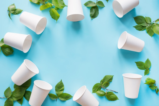 Border of white disposable cup and green leaves on blue