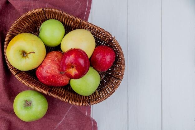 Bordo布とコピースペースを持つ木製の背景上のバスケットにリンゴのトップビュー