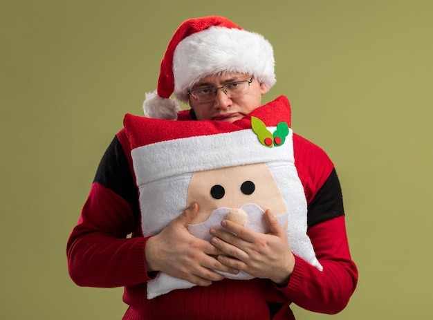 Скучно взрослый мужчина в очках и шляпе санта-клауса держит подушку санта-клауса сзади, изолированную на оливково-зеленой стене