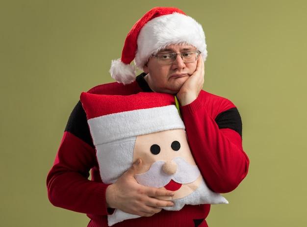 Скучно взрослый мужчина в очках и шляпе санта-клауса держит подушку санта-клауса, держа руку на лице, глядя в сторону, изолированную на оливково-зеленой стене