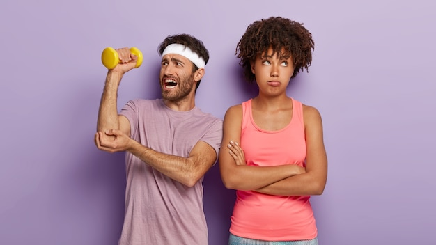 Bored afro woman keeps arms folded, being tired of going in for sport and hard working motivated man works on muscles, holds dumbbell