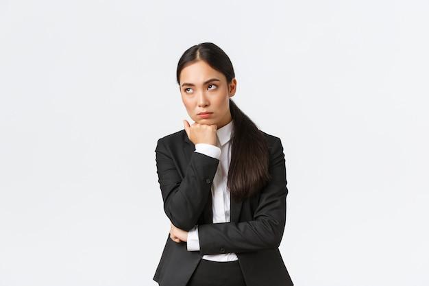 Скучающая и раздраженная женщина-предприниматель, которая безразлично смотрит в сторону, сидя на скучной встрече, посещает неинтересные офисные собрания, стоит на белом фоне, умирает от скуки