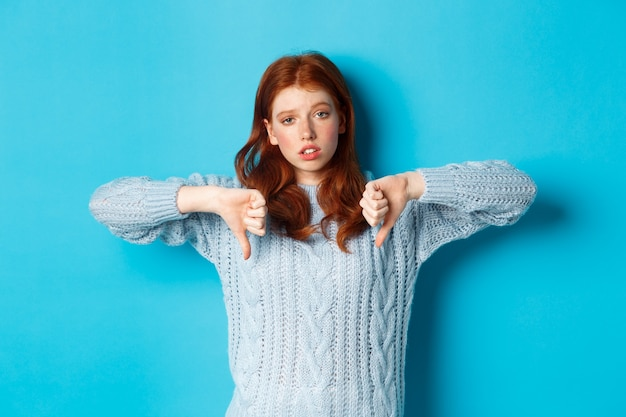 退屈で懐疑的な赤毛の女の子が親指を下に向けて、面白くなく、興味がないように見え、青い背景の上に立っています。