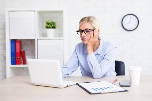 Скучно и усталая деловая женщина, работающая с компьютером в офисе