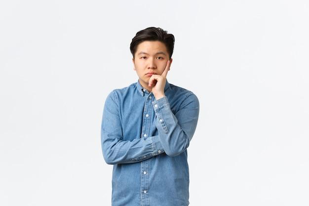 青いシャツを着た退屈で無関心なアジア人男性、カメラを面白がらず不注意に見ている、退屈なスピーチを聞いている、白い背景の上に不機嫌でイライラしている、人にうんざりしている。