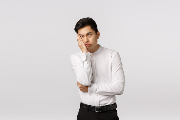 Bored and annoyed young asian businessman dying from boredom and annoyance, roll eyes up, facepalm, lean face on hand and waiting when meeting over, standing irritated