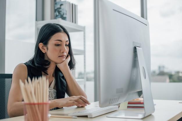 Скучающая азиатская бизнесвумен, незаинтересованная в рутинной монотонной работе