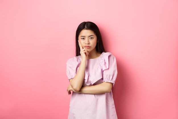 Bored asian teen girl look indifferent at camera, lean face on hand in skeptical pose, standing reluctant against pink background.
