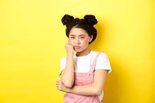 Скучающая азиатская девушка-подросток со стильным макияжем и летней одеждой, выглядящая неохотно и равнодушно, стоит на желтом.