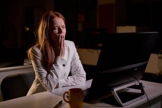 Скучно на офисной работе, сонная женщина-работник, отдыхающая на рабочем месте, немотивированный ленивый офисный работник, рыжая дама, чувствуя себя сонной, засыпающей, зевая возле компьютера, скучная работа и концепция отсутствия сна