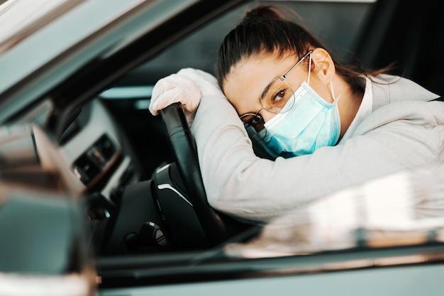 コロナウイルスの発生中に交通渋滞で立ち往生しているステアリングホイールに寄りかかってゴム手袋をしたフェイスマスクで退屈な魅力的なブルネット。