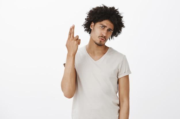 Скучающий привлекательный мужчина дует себе мозги, делая жест рукой пистолет от раздражения