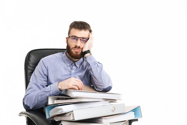 Скучно бородатый элегантный мужчина в очках сидит на кресле с папками и смотрит