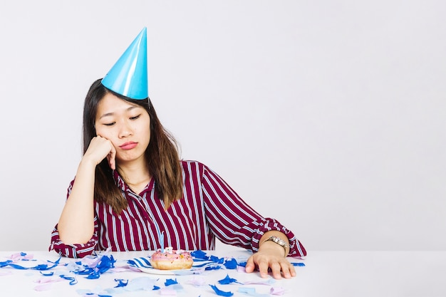 Ragazza annoiata di compleanno con ciambella