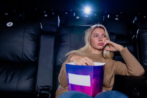 Скучающая блондинка с коробкой попкорна сидит на черном кожаном кресле перед большим экраном в кинотеатре и смотрит фильм