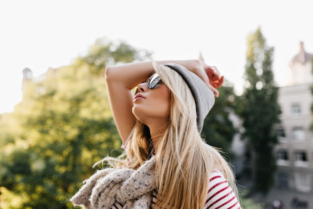 Bored blonde woman in hat and scarf looking at sky while walking at the street
