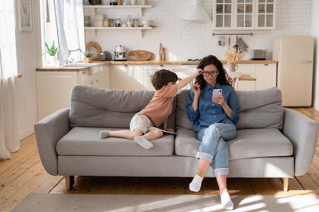 지루한 소년은 스마트폰으로 메시지를 읽는 엄마 성가신 사업가를 방해하고 엄마의 관심이 필요합니다.