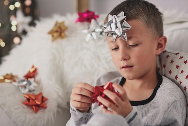 クリスマスに肘掛け椅子に座っている退屈な少年