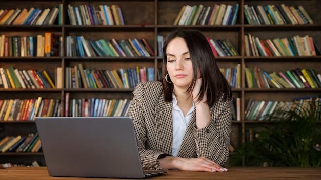 짧은 느슨한 머리를 가진 지루한 갈색 머리는 사무실 책장에 대 한 갈색 테이블에 머리를 들고 회색 노트북 디스플레이를 본다
