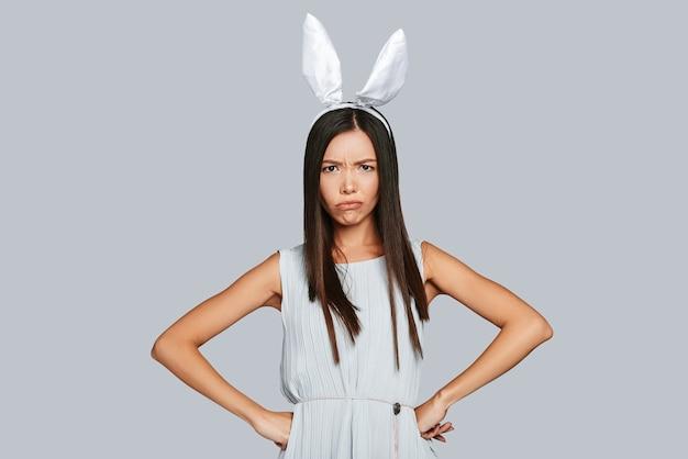 Скучающий кролик. сердитая молодая азиатская женщина в кроличьих ушах смотрит в камеру, стоя на сером фоне