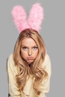 Скучающий кролик. привлекательная молодая женщина в розовых кроличьих ушах гримасничает и смотрит в камеру, стоя на сером фоне