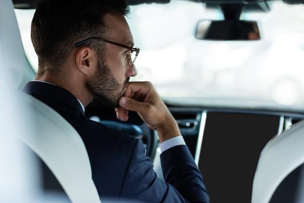 退屈なビジネスマン。渋滞で待っている間、眼鏡をかけているビジネスマンは退屈を感じます
