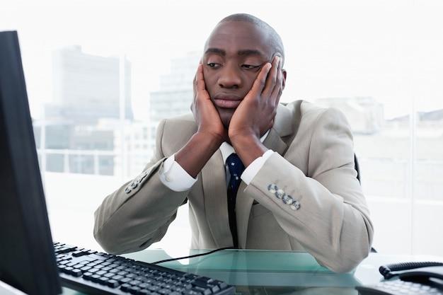 Скучно бизнесмен смотрит на свой компьютер