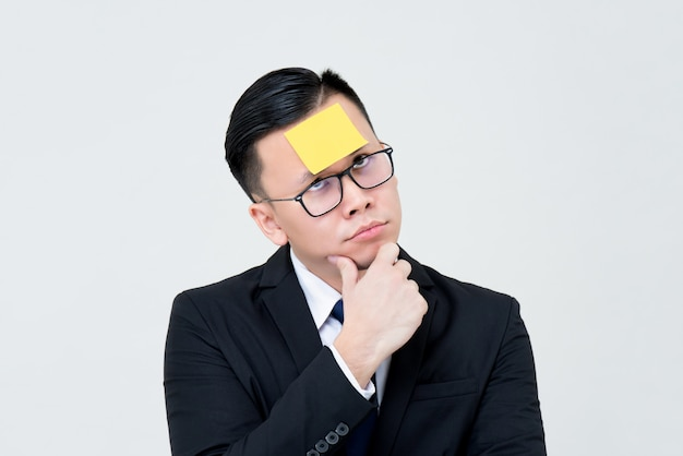 Bored businessman thinking with sticky note paper on forehead