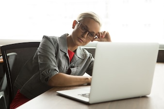 Bored businesswoman in glasses working at laptop