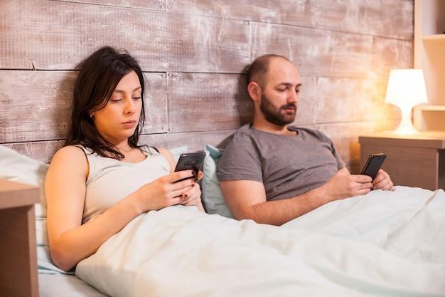 スマートフォンでブラウジングして寝る前に退屈な白人カップル。