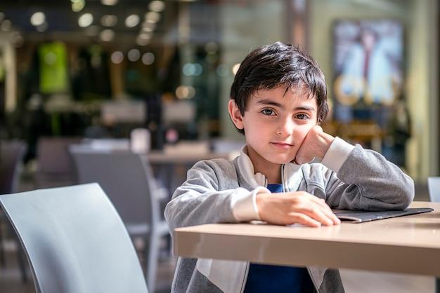 退屈な子供がショッピングモールのレストランのテーブルで待つ