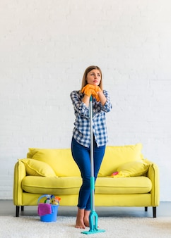 Bored contemplated young woman holding mop standing in the living room