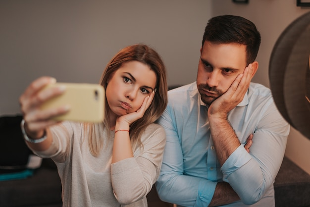 Bored couple taking funny selfie.