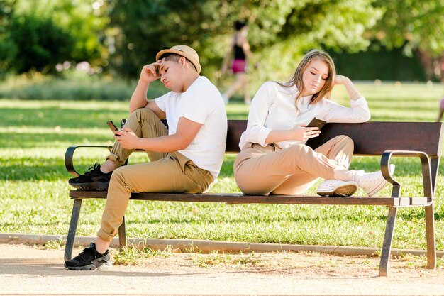 Bored couple using their mobile phones in a public park