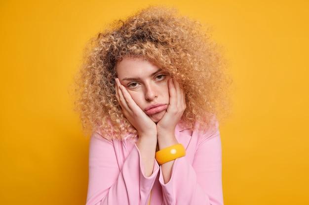 지루한 불쾌한 여자가 뺨에 손을 댄다. 지루한 비즈니스 회의를 좋아하지 않는 정보가 재미없는 정보가 분홍색 재킷 팔찌를 착용하고 노란색 벽 위에 고립 된 덤불 같은 곱슬 머리가 있습니다.