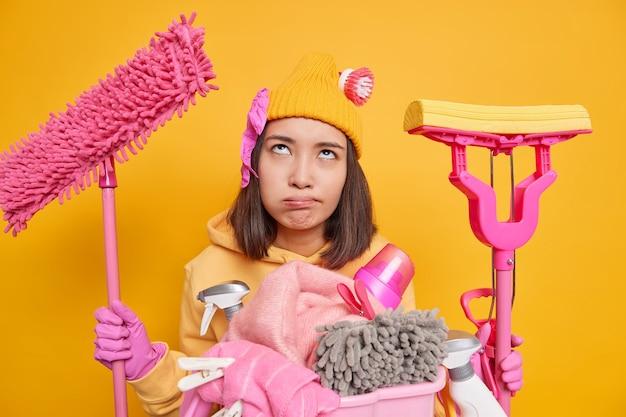 毎日の掃除にうんざりしている不幸な上に集中している退屈な不満のアジアの主婦は、ゲストが訪れる前に、帽子のスウェットシャツのゴム手袋を身に着けているモップを手に持っています