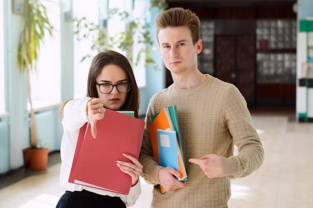 책과 학습 자료를 가지고 대학 홀에서 포즈를 취하는 지루한 산만 한 학생들