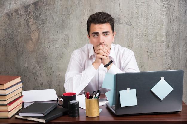 사무실 책상에서 일을 끝내고 싶어하는 지루한 직원.