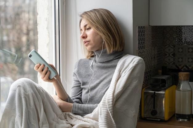 집 창턱에 앉아 휴대폰으로 소셜 미디어에서 채팅하는 지루한 여성
