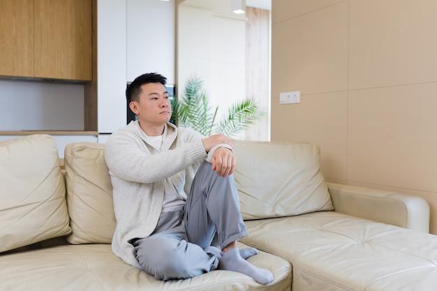 一人で自宅のソファに座っている退屈な友人若いアジア人