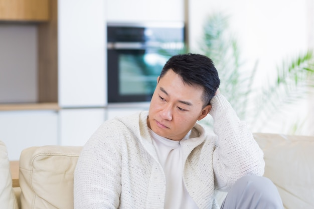 Bored friends young asian man sitting on sofa at home alone